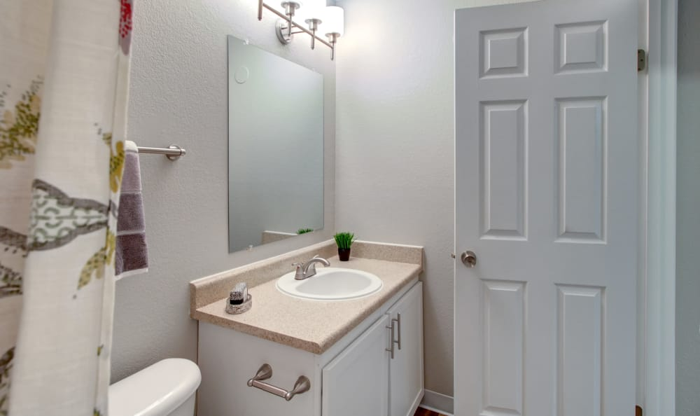 Bathroom with large vanity mirror in apartment home at The Boulevard at South Station Apartment Homes in Tukwila, Washington