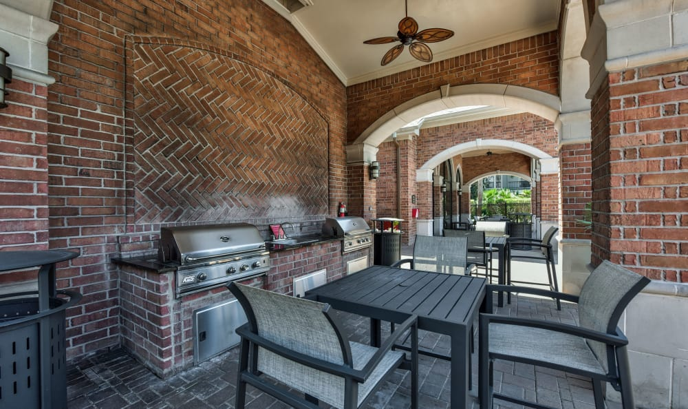 Covered barbecue area with ceiling fans and plenty of seating at San Paloma Apartments in Houston, Texas