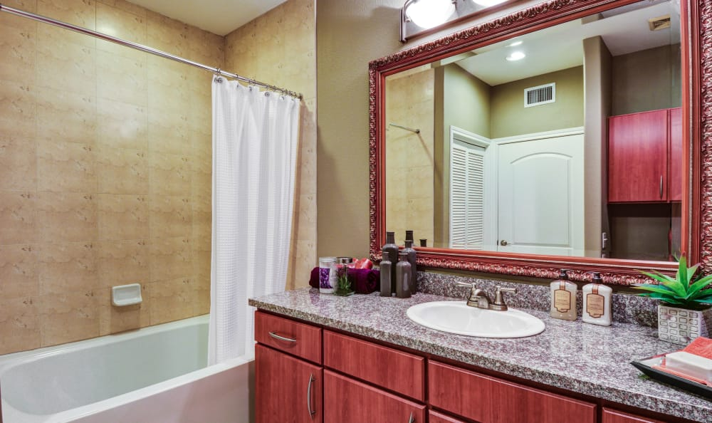 Well-lit bathroom with large vanity mirror and granite countertop in model home at San Paloma Apartments in Houston, Texas
