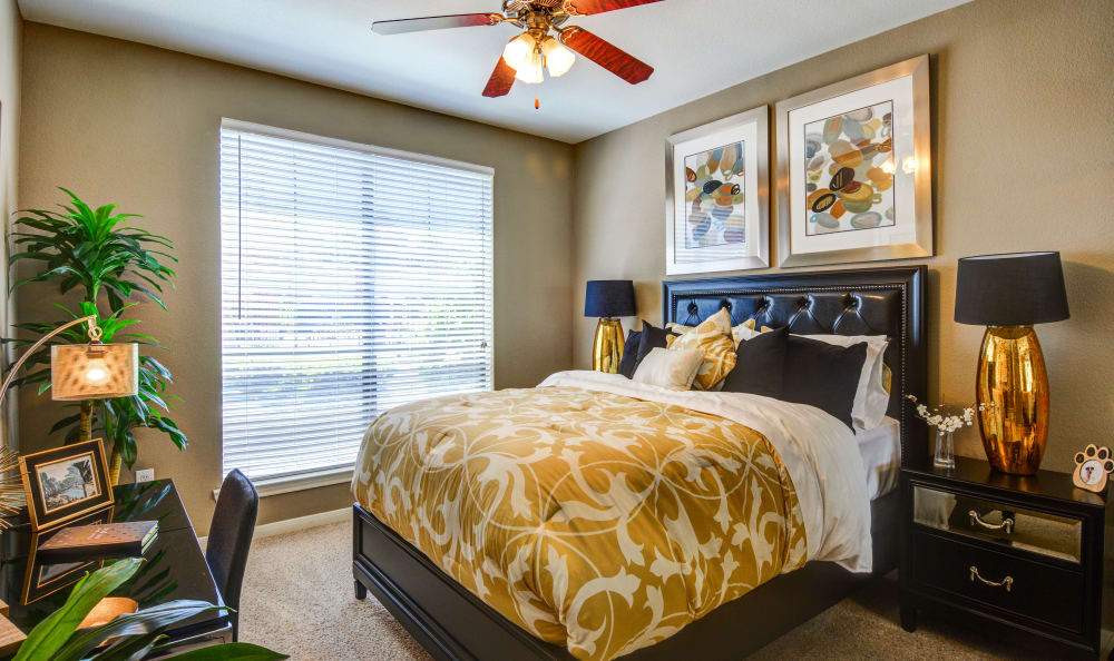 Large master bedroom with ceiling fan and contemporary decor in model home at San Paloma Apartments in Houston, Texas