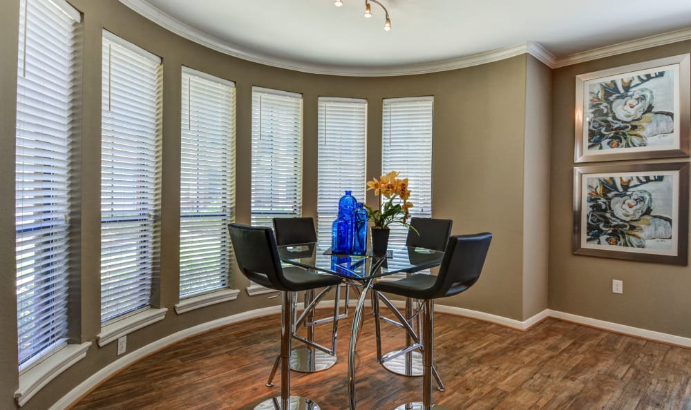 Dining nook with panoramic floor-to-ceiling windows and hardwood floors in model home at San Paloma Apartments in Houston, Texas