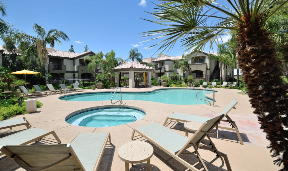 Chaise lounge chairs surrounding the hot tub and pool area at Lumiere Chandler in Chandler, Arizona