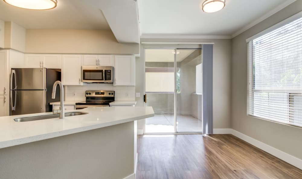 Beautiful hardwood floors in living area next to kitchen of model home at Lumiere Chandler in Chandler, Arizona
