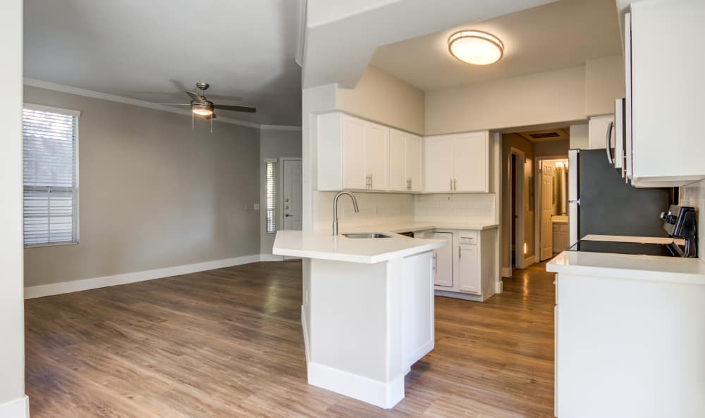 Hardwood floors in living area and kitchen of open-concept apartment home at Lumiere Chandler in Chandler, Arizona