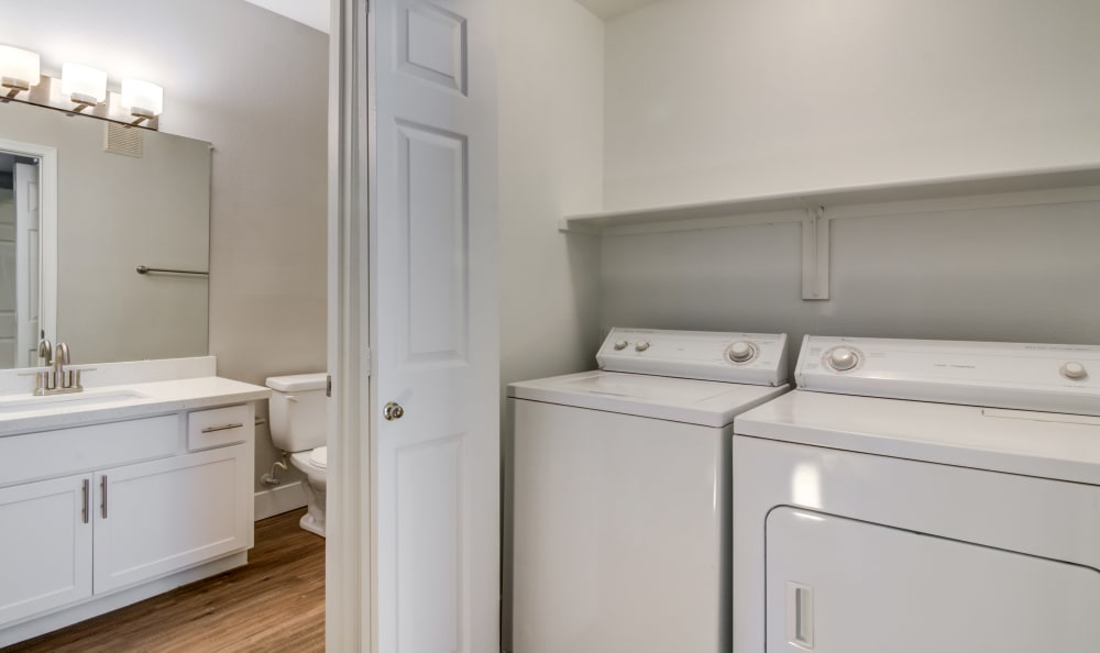 In-unit washer and dryer with adjacent bathroom in model home at Lumiere Chandler in Chandler, Arizona