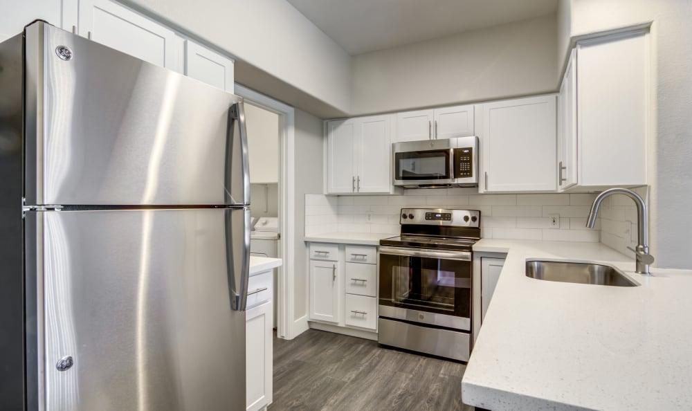 Hardwood floor and subway tile backsplash in model home's kitchen at Lumiere Chandler in Chandler, Arizona