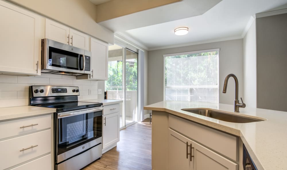 Stainless-steel appliances and white cabinetry in model home's kitchen at Lumiere Chandler in Chandler, Arizona