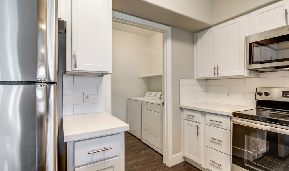 Gourmet kitchen with adjacent laundry room in model home at Lumiere Chandler in Chandler, Arizona