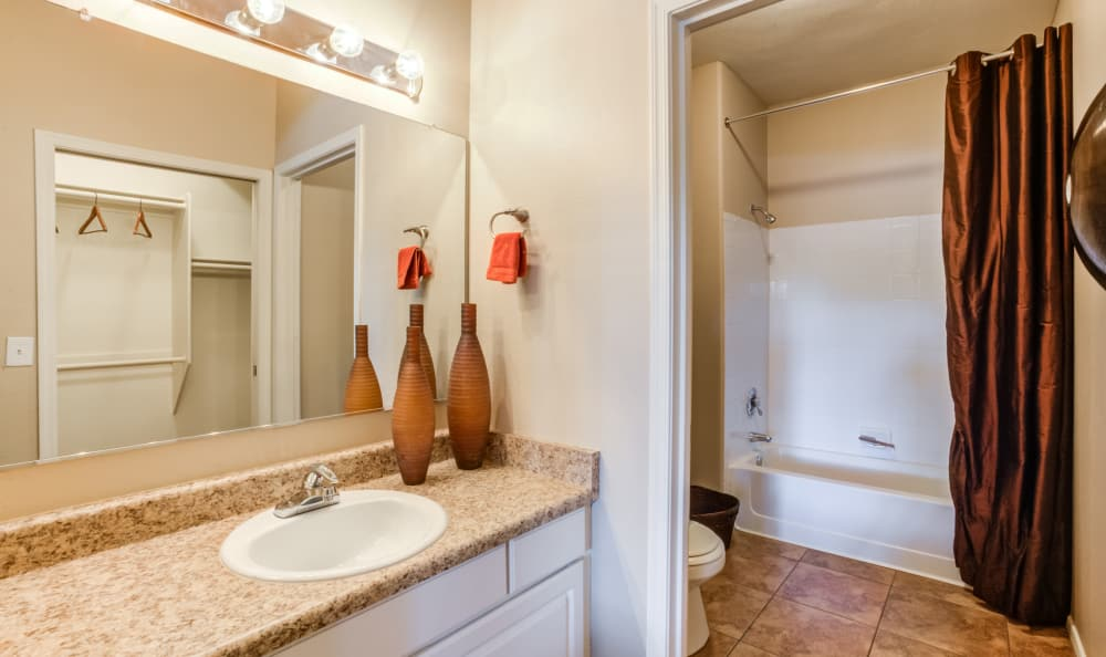 Bathroom with granite countertop and a large vanity mirror in a model home at Finisterra in Tempe, Arizona