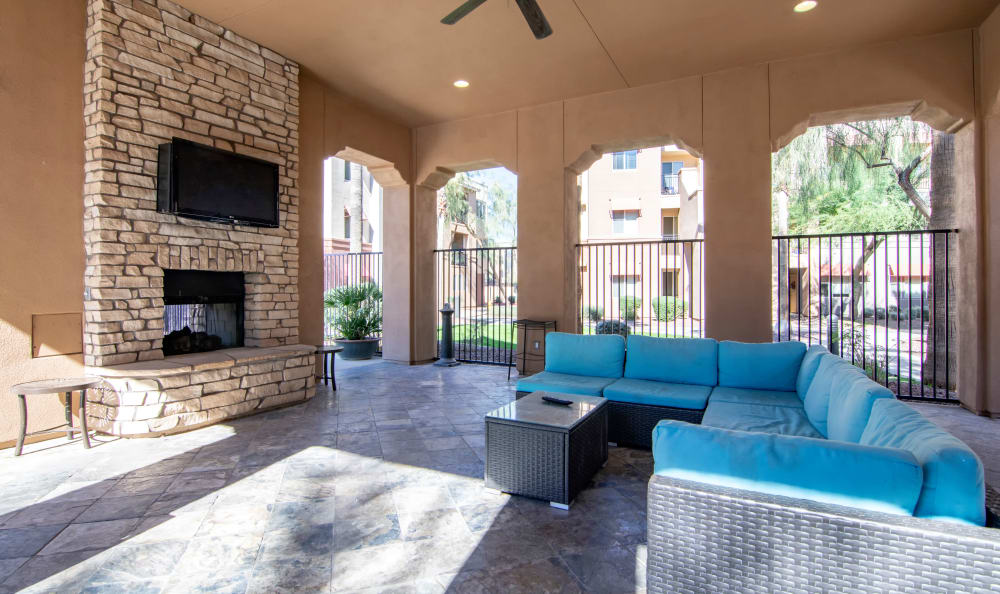 Fireplace and flatscreen TV in covered outdoor cabana at The Residences at Stadium Village in Surprise, Arizona