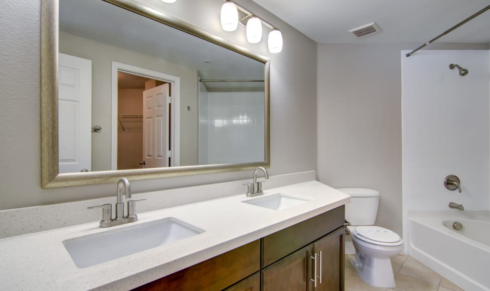 Large vanity mirror in well-lit bathroom of apartment home at The Residences at Stadium Village in Surprise, Arizona