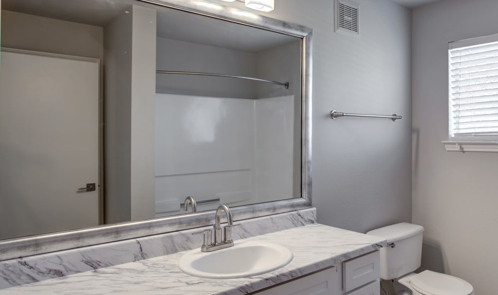 Granite countertop and large vanity mirror in renovated home's bathroom at Kenwood Club at the Park in Katy, Texas