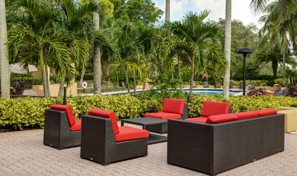 Comfortable lounge seating surrounded by lush flora at one of the outside common areas at IMT Pinebrook Pointe in Margate, Florida