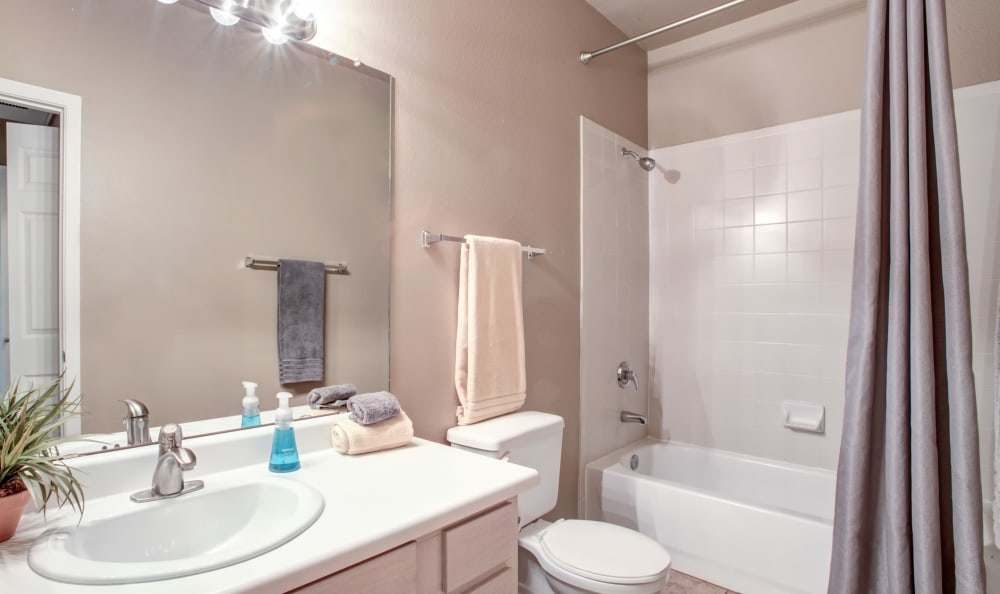 Well-lit bathroom with a large vanity mirror in a model home at Sierra Canyon in Glendale, Arizona