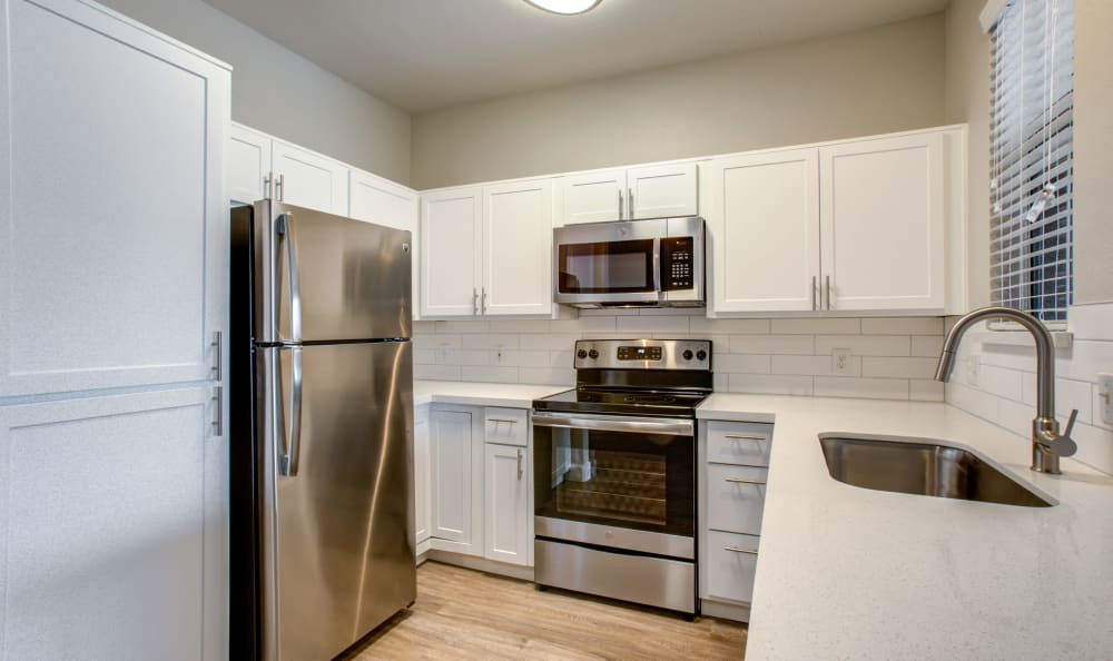 Gourmet kitchen with stainless-steel appliances in a recently renovated apartment home at Sierra Canyon in Glendale, Arizona