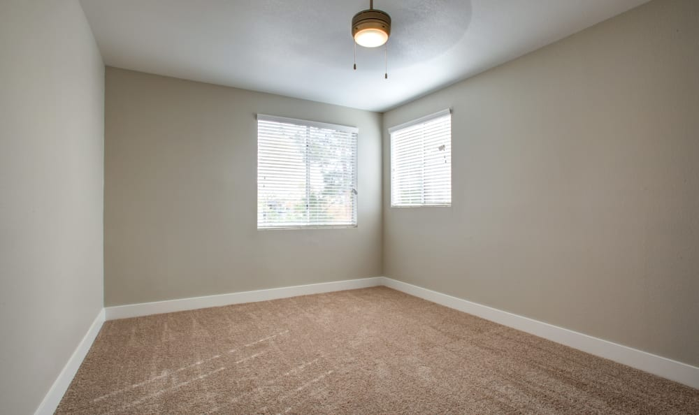 Plush carpeting and a ceiling fan in the guest bedroom of an apartment home at Sierra Canyon in Glendale, Arizona