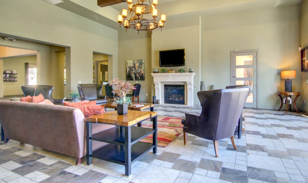 Comfortable seating in front of the fireplace and flatscreen TV in the resident clubhouse at The Residences at Stadium Village in Surprise, Arizona