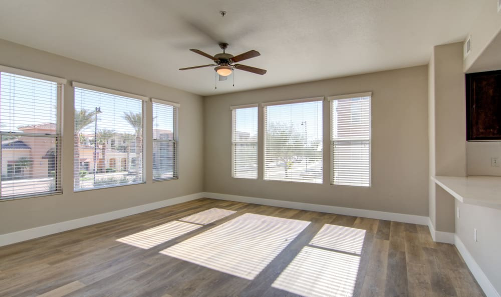 Hardwood floors and a ceiling fan in a recently renovated apartment home at The Residences at Stadium Village in Surprise, Arizona