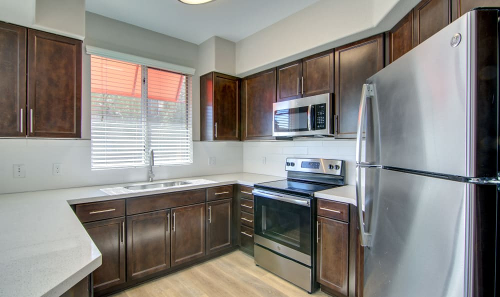 Dark wood cabinetry and stainless-steel appliances in a recently renovated apartment home's kitchen at The Residences at Stadium Village in Surprise, Arizona