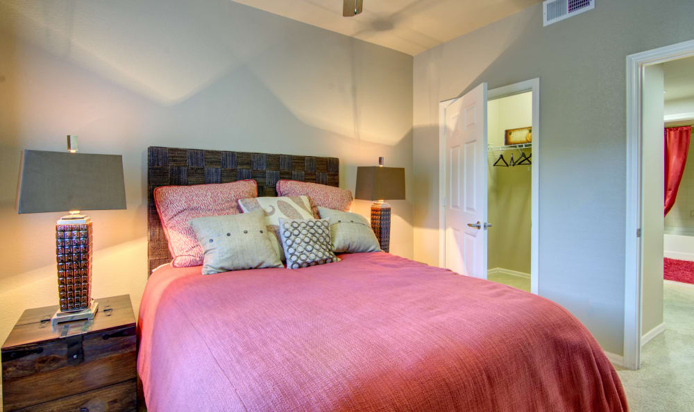 Well-decorated master bedroom with a walk-in closet and an en suite bathroom in model home at The Residences at Stadium Village in Surprise, Arizona