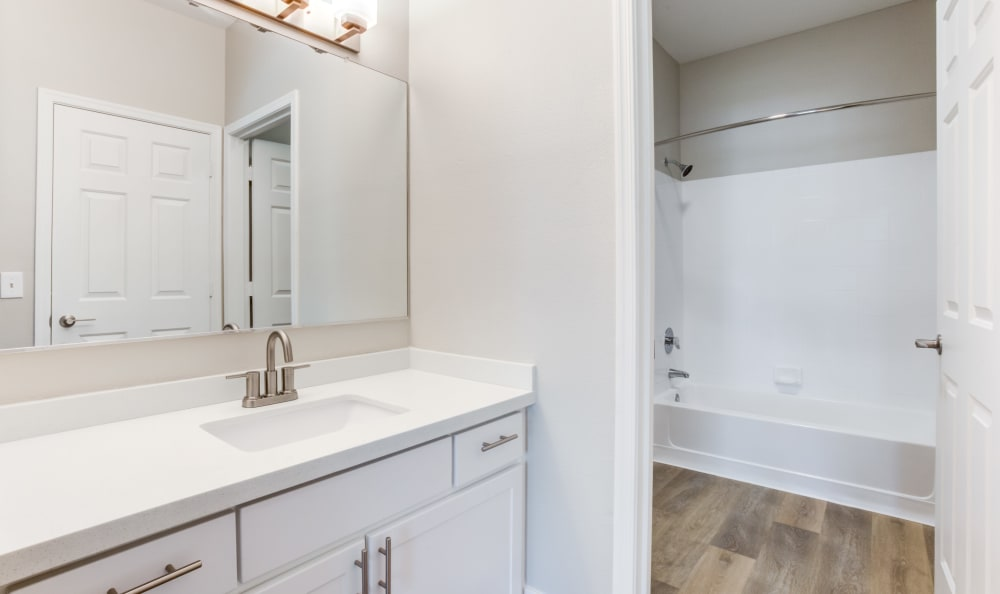 Hardwood floors and a granite countertop in the master bathroom of an apartment home at Finisterra in Tempe, Arizona