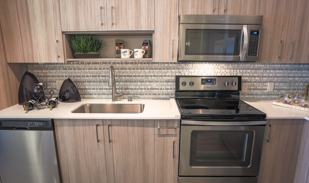 Granite countertops and modern appliances in a model home's kitchen at Loftin Place Apartments in West Palm Beach, Florida