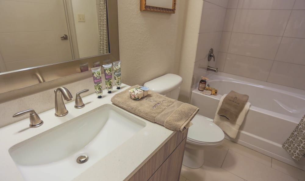 Bathroom with a tiled shower and oval bathtub in a model home at Loftin Place Apartments in West Palm Beach, Florida