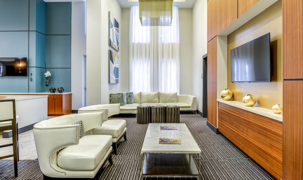 Luxurious lobby interior with lounge seating in front of the flatscreen TV at Loftin Place Apartments in West Palm Beach, Florida