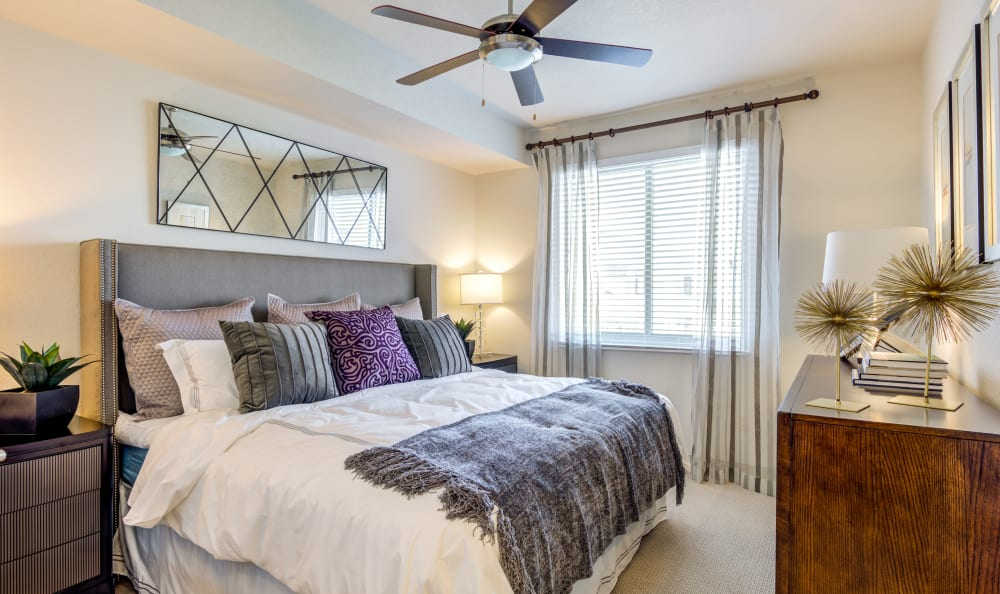 Well-decorated master bedroom with a ceiling fan in a model home at Loftin Place Apartments in West Palm Beach, Florida