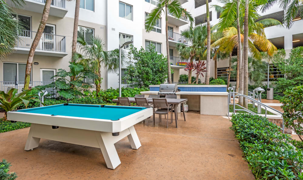 Outdoor games and barbecue area with gas grills near the pool at Loftin Place Apartments in West Palm Beach, Florida