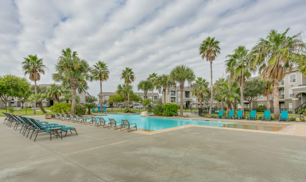 Resort-style swimming pool area with chaise lounge chairs at Azure Apartments in Corpus Christi, Texas
