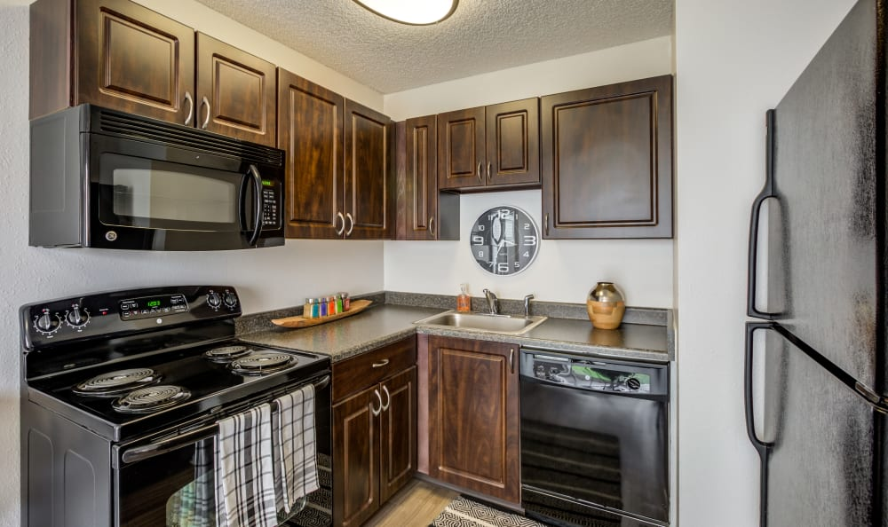 Gourmet kitchen with granite countertops and black appliances in a model townhome at Stratus Townhomes in Westminster, Colorado