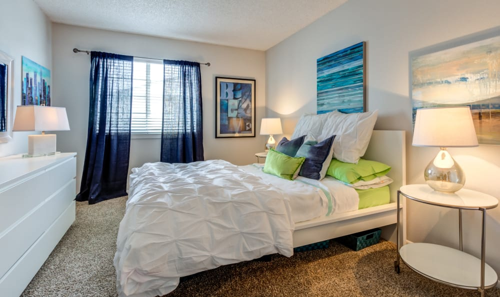 Well-decorated master bedroom with plush carpeting in a model townhome at Stratus Townhomes in Westminster, Colorado