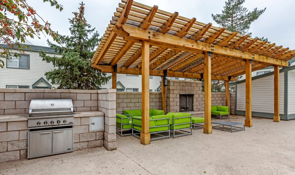 Barbecue area with gas grills and lounge seating under a pergola at Stratus Townhomes in Westminster, Colorado