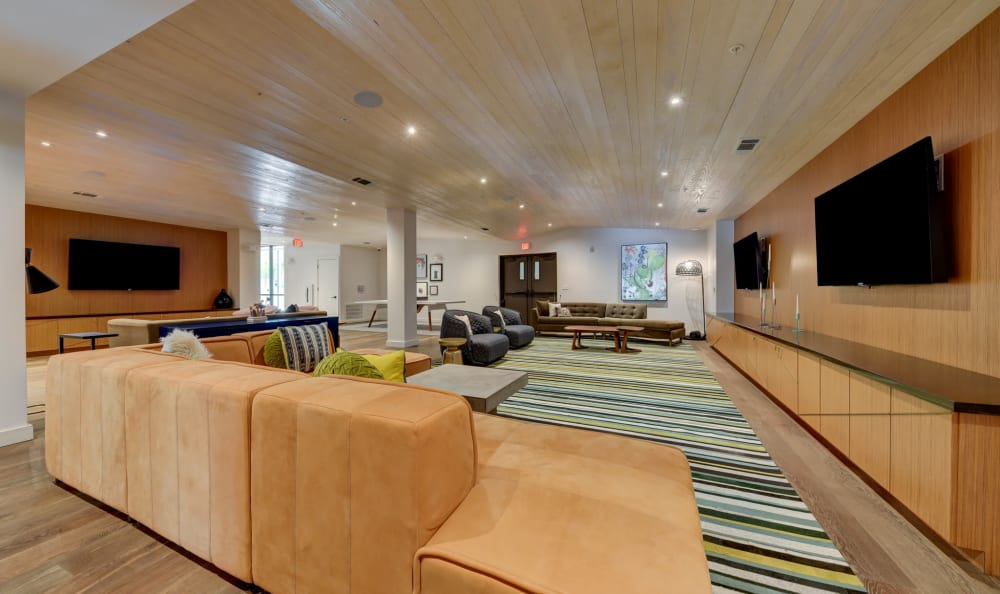 Community lounge with ample seating and large flat-screen TVs at Agave in San Antonio, Texas