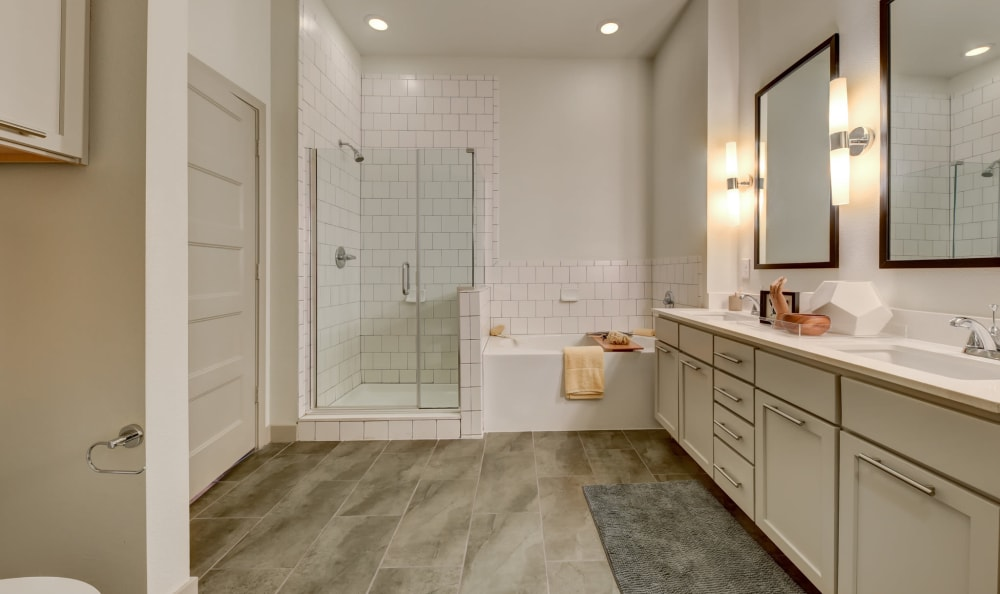 Large bathroom with a tiled shower and vanity mirrors at Agave in San Antonio, Texas