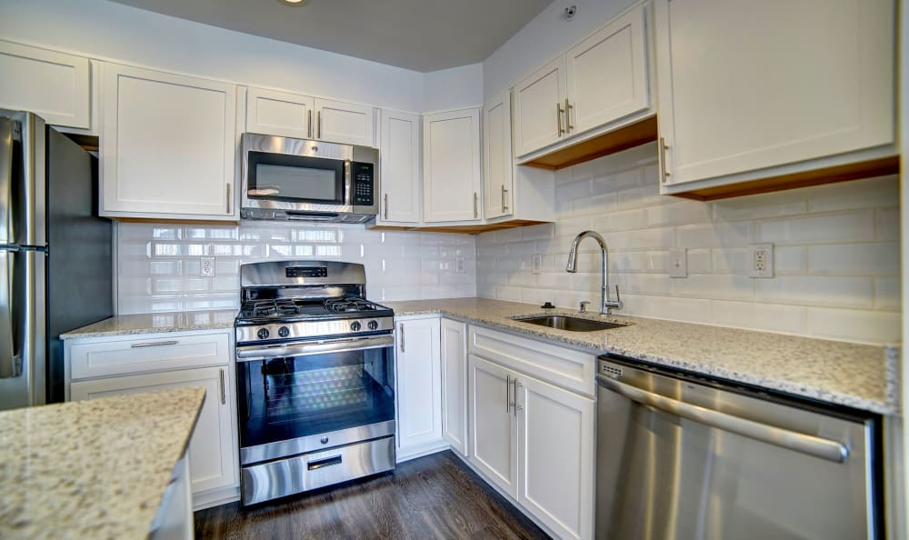 Kitchen with a subway tile backsplash and stainless-steel appliances in a model home at Watergate Pointe in Annapolis, Maryland
