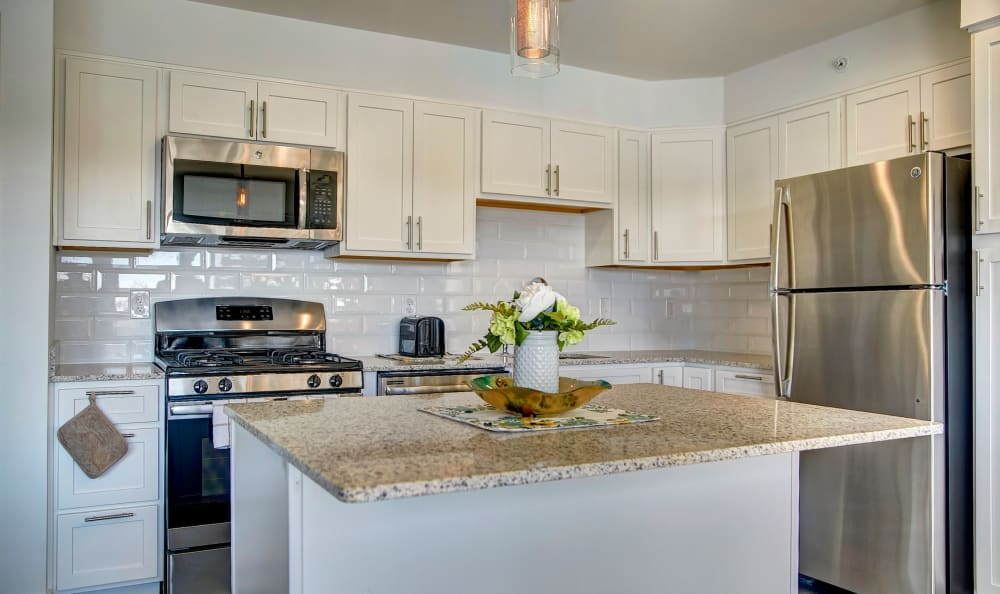 Gourmet kitchen with granite countertops and white cabinetry in a model home at Watergate Pointe in Annapolis, Maryland
