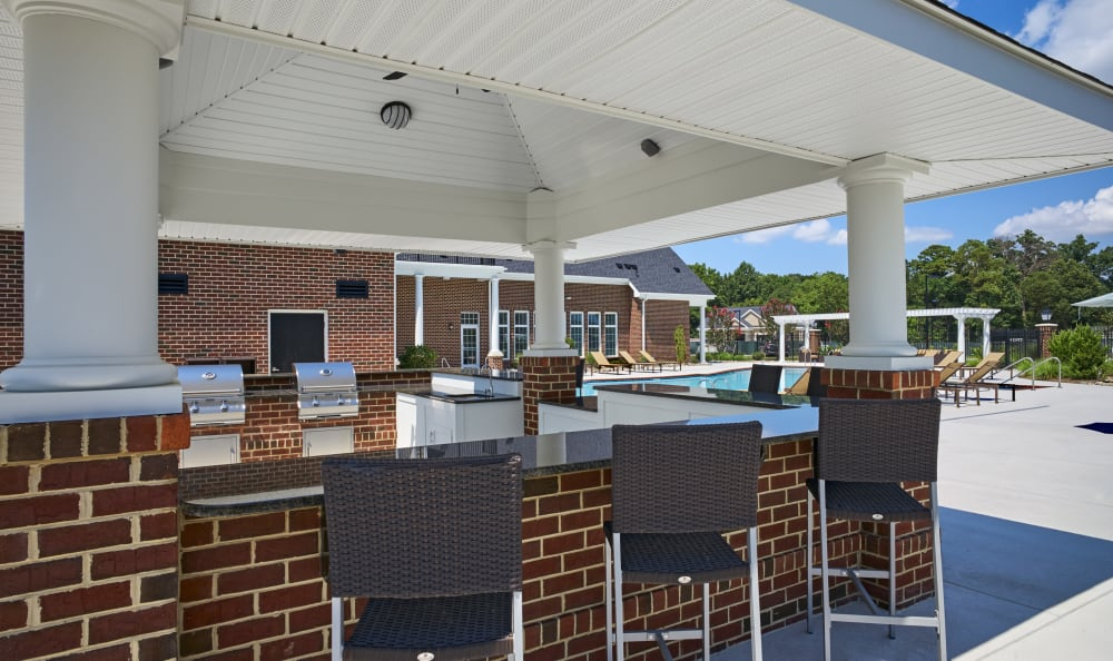 Outdoor community barbecue area with bar seating at Meridian Obici in Suffolk, Virginia