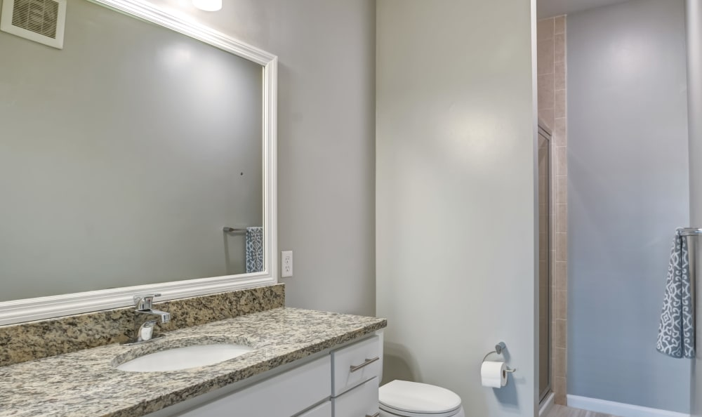Bathroom with granite counter tops and a large vanity mirror at Harbor Pointe in Bayonne, New Jersey