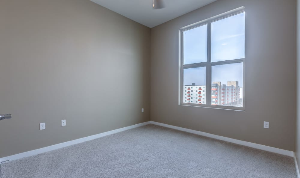 Large bedroom with plush carpeting at Lumen Apartments in Everett, Washington