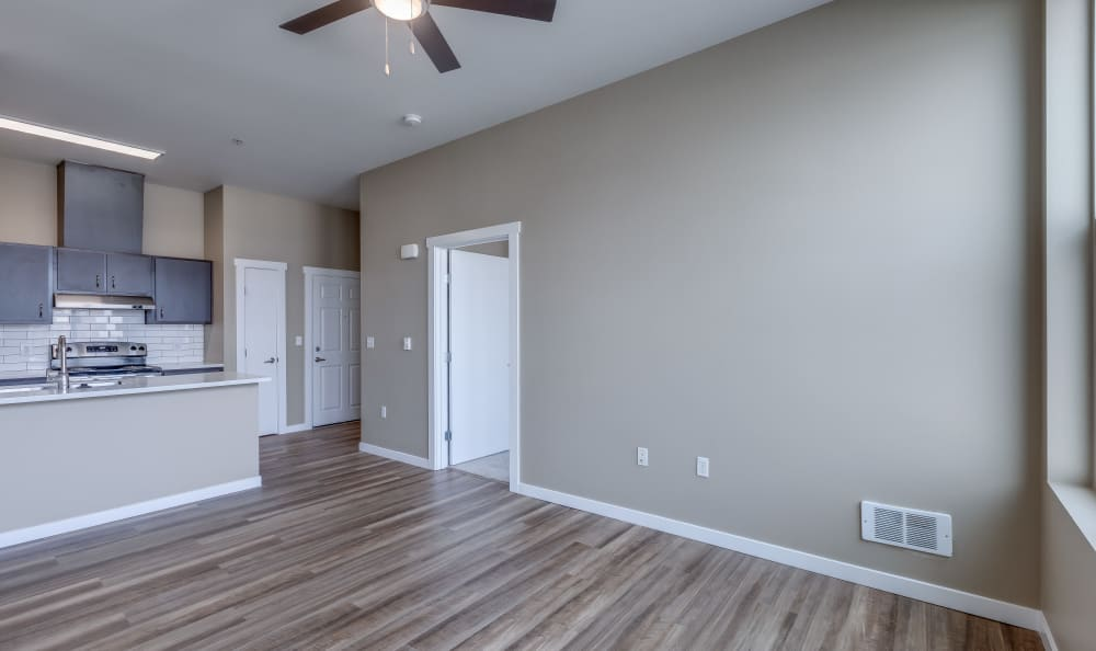 Living room with wood-styled floors and a ceiling fan at Lumen Apartments in Everett, Washington