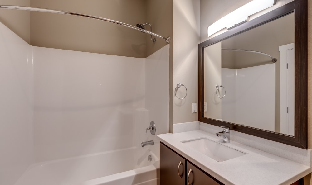 Bathroom with ample counter space and a large vanity mirror at Lumen Apartments in Everett, Washington