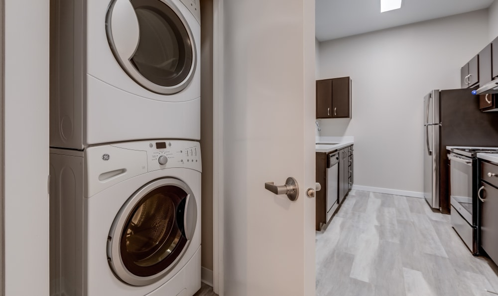 Stacked washer and dryers provided at Lumen Apartments in Everett, Washington