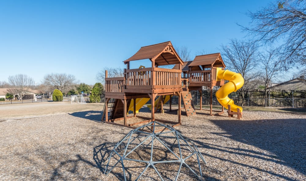 Children's playground with a slide at Sage at 1825 Apartments in Pflugerville, Texas