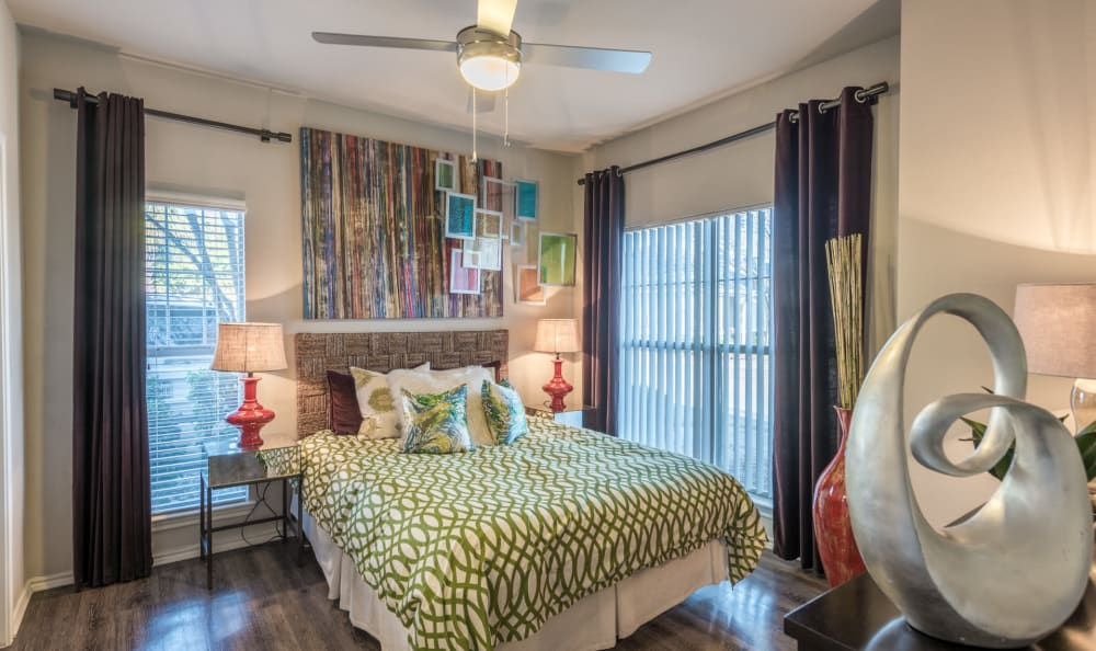 A master bedroom with ceiling fan and two large windows at Sage at 1825 Apartments in Pflugerville, Texas