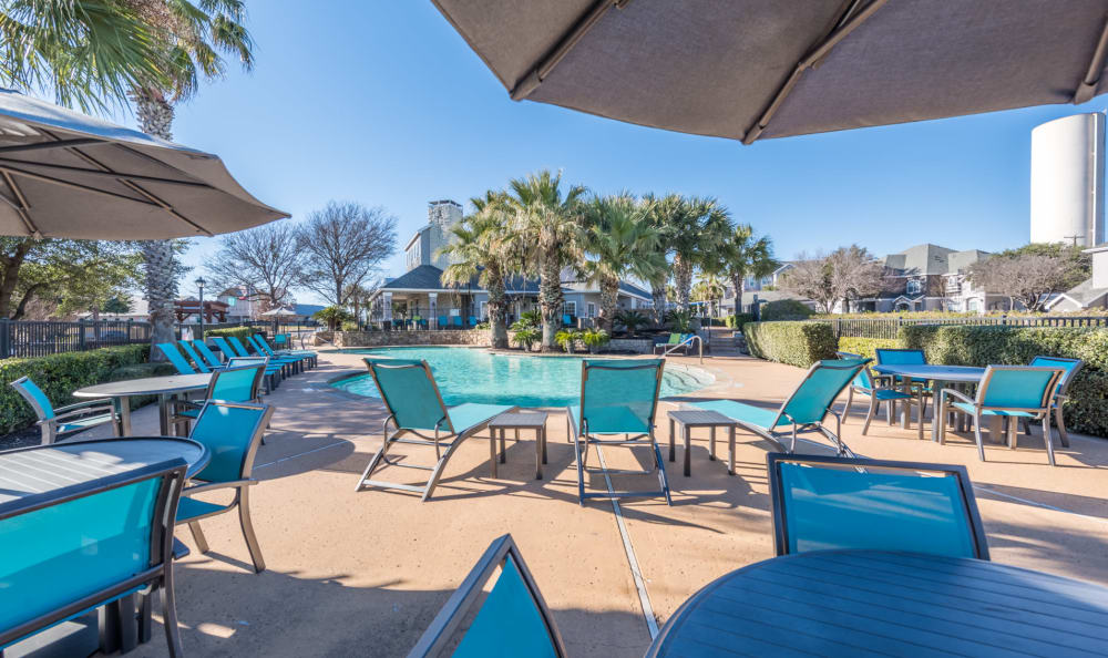 Poolside sundeck with ample seating for outdoor lunches at Sage at 1825 Apartments in Pflugerville, Texas