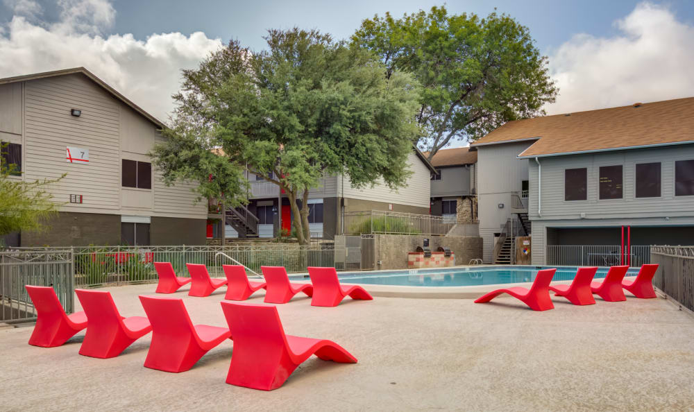 Large swimming pool with a sundeck and plenty of lounge chairs at Array Apartments in Austin, Texas