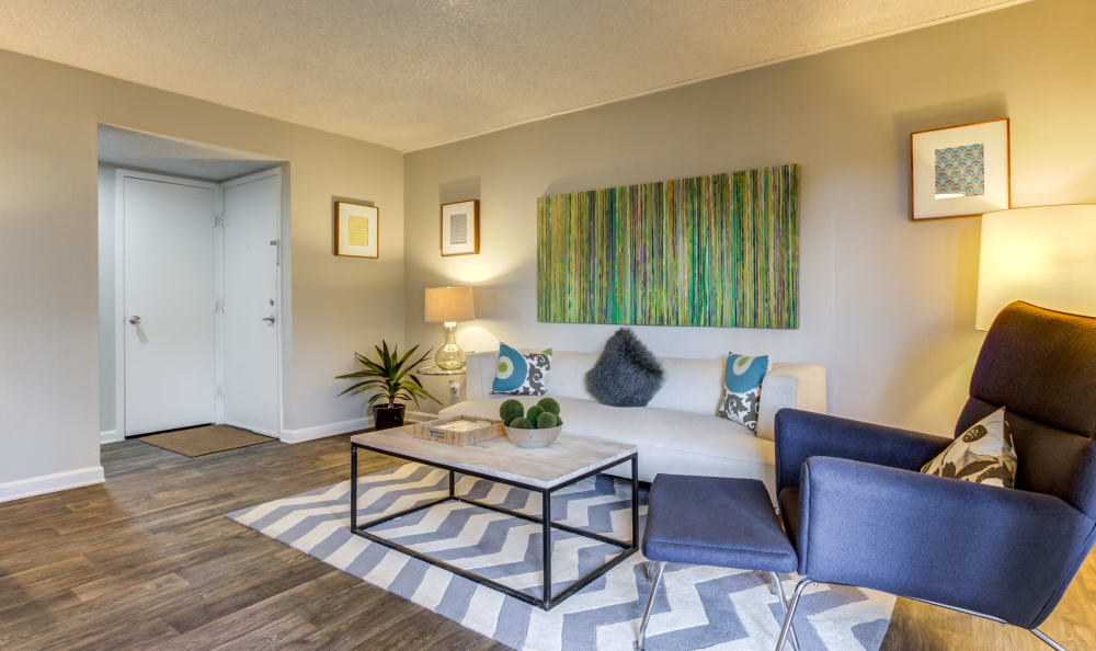 Model home's living area with hardwood floors at The Ranch at Bear Creek Apartments & Townhomes in Lakewood, Colorado