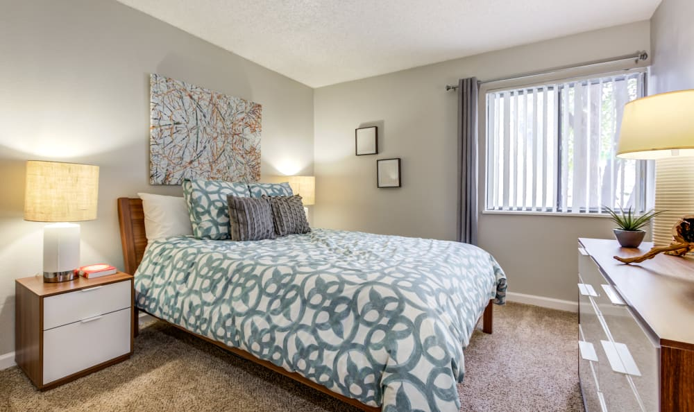 Plush carpet and large windows for ample natural light in a model home's master bedroom at The Ranch at Bear Creek Apartments & Townhomes in Lakewood, Colorado